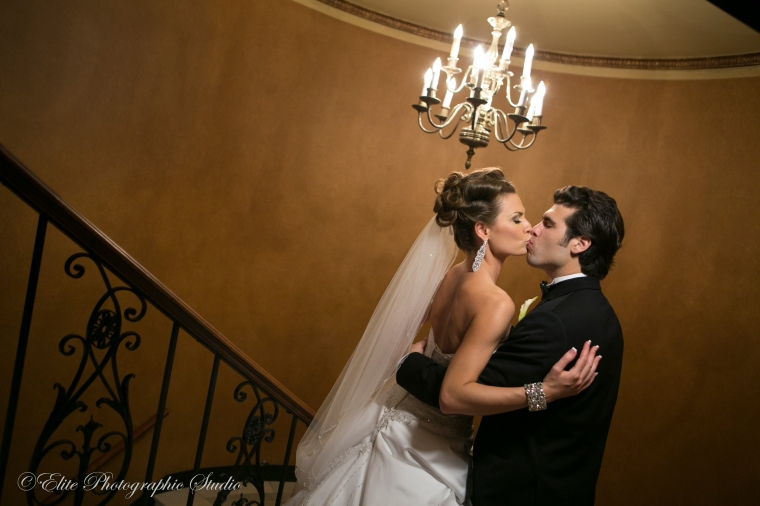 Bride and groom kiss on the staircase of the Colony Club in Detroit
